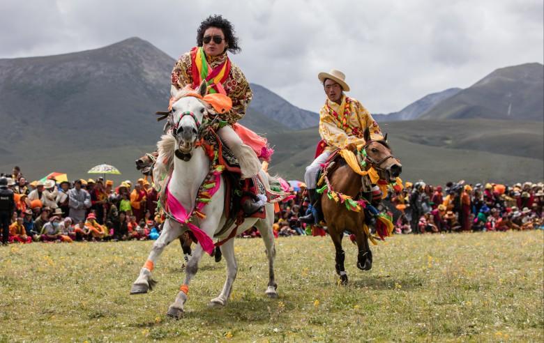 Ryttare under hästfestivalen väster om Litang